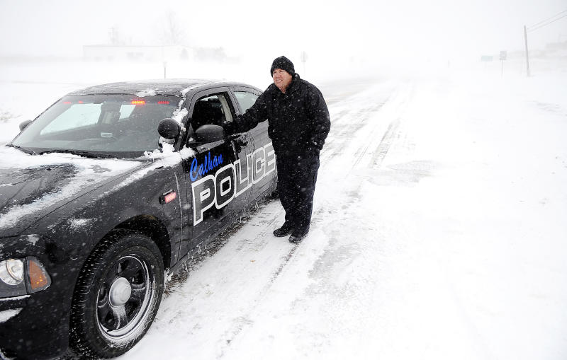 Calhan Police Sgt. Josh Morrision stands by his car as he blocks Eastbound traffic on Highway 24 outside of Calhan, Colo. as blowing snow and slick roads closed the highway Saturday, March 23, 2013. Transportation officials said Interstate 70 was closed from Denver to Colby, Kan., on Saturday. The National Weather Service said the Denver area could see up to 7 inches of snow Saturday. (AP Photo/The Colorado Springs Gazette, Michael Ciaglo) MAGS OUT