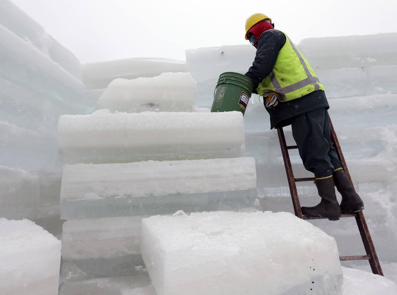 Naquan Shideo from the Brooklyn borough of New York, an inmate at the Moriah Shock Incarceration Correctional Facility, uses slush water to seal ice blocks while helping construct the Saranac Lake Winter Carnival ice palace on Monday, Jan. 28, 2013, in Saranac Lake, N.Y. (AP Photo/Mike Groll)