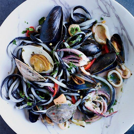 """<p>F&W Best New Chef Eli Kulp prepares this dramatic seafood pasta dish with freshly made, toothsome black-and-white noodles, which he tosses with a big, briny seafood sauce and finishes with spicy pickled cherry peppers.</p><p><a href=""""https://www.foodandwine.com/recipes/black-and-white-pici-pasta-squid-and-shellfish"""">GO TO RECIPE</a></p>"""