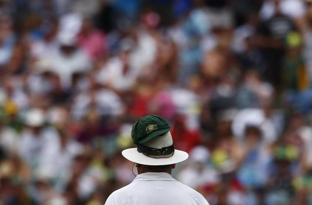 Australia's Nathan Lyon's cap is seen on umpire Marais Erasmus's hat as he bowls during the fourth day of the second Ashes test cricket match against England at the Adelaide Oval December 8, 2013. REUTERS/David Gray (AUSTRALIA - Tags: SPORT CRICKET TPX IMAGES OF THE DAY)