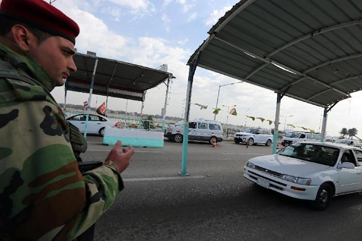 A member of the Iraqi security forces mans a checkpoint on the main road from Baghdad's central Jaderiyah district to Dura, on January 18, 2016 (AFP Photo/Sabah Arar)