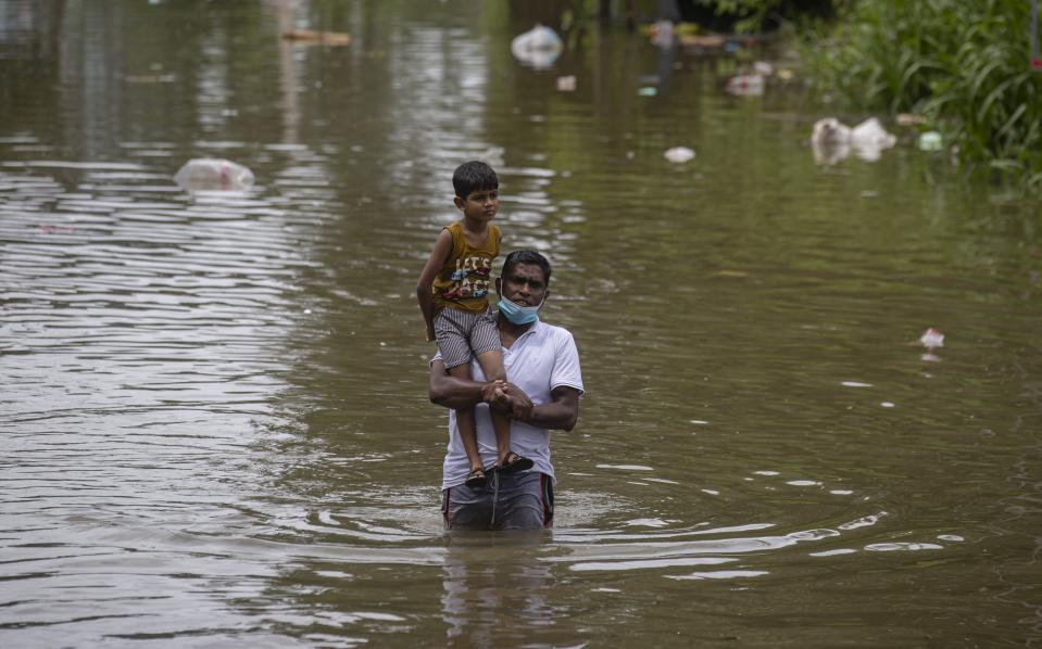 A Sri Lankan man wades through in an inundated street carrying a child following heavy rainfall at Malwana, on the outskirts of Colombo, Sri Lanka, Saturday, June 5, 2021. Flash floods and mudslides triggered by heavy rains in Sri Lanka have killed at least four people and left seven missing, while more than 5,000 are displaced, officials said Saturday. Rains have been pounding six districts of the Indian Ocean island nation since Thursday night, and many houses, paddy fields and roads have been inundated, blocking traffic. (AP Photo/Eranga Jayawardena)