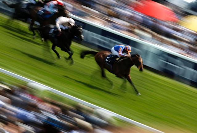 Stravagante ridden by Ryan Moore takes the lead during The Private Banking Stakes horse race on the second day of the Epsom Derby Festival in Surrey, England, on June 6, 2015 (AFP Photo/Adrian Dennis)