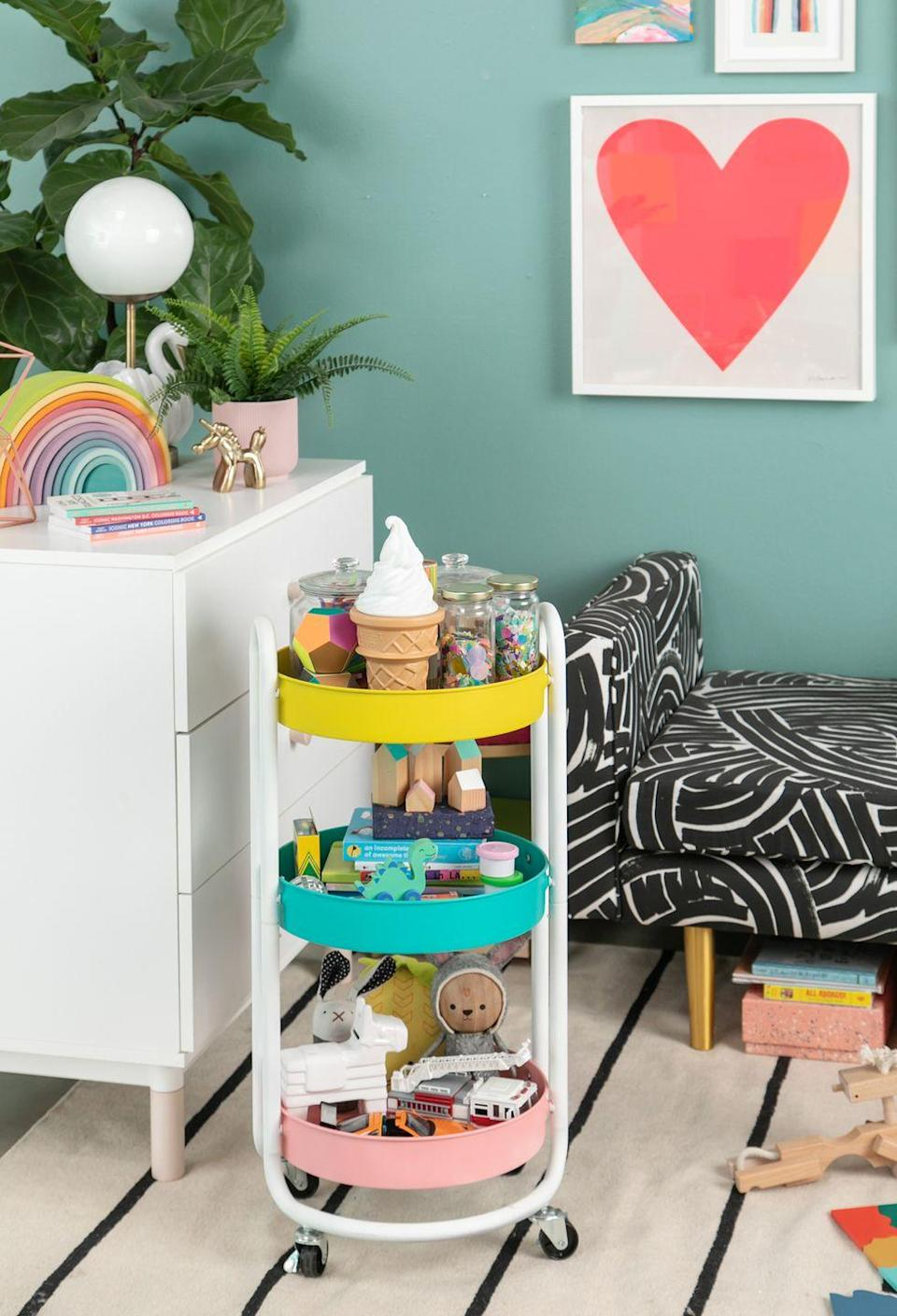 """<p>Have your kiddos help clean up by giving them a cute cart to load up with their toys from around the house and take back to the playroom.</p><p><strong>See more at </strong><strong><a href=""""https://ohjoy.blogs.com/my_weblog/2019/02/a-play-room-to-grow-with.html"""" rel=""""nofollow noopener"""" target=""""_blank"""" data-ylk=""""slk:Oh Joy"""" class=""""link rapid-noclick-resp"""">Oh Joy</a>.</strong></p><p><strong><a class=""""link rapid-noclick-resp"""" href=""""https://www.amazon.com/BEEY-Utility-Trolley-Organizer-Barbecue/dp/B08F3D97RJ/ref=sr_1_7?dchild=1&keywords=round+rolling+cart&qid=1613589329&s=office-products&sr=1-7&tag=syn-yahoo-20&ascsubtag=%5Bartid%7C10063.g.36014277%5Bsrc%7Cyahoo-us"""" rel=""""nofollow noopener"""" target=""""_blank"""" data-ylk=""""slk:SHOP ROLLING CARTS"""">SHOP ROLLING CARTS</a><br></strong></p>"""