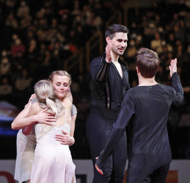 Russia's Victoria Sinitsina and Nikita Katsalapov, back to camera, greet Madison Hubbell and Zachary Donohue of the U.S. during the medal ceremony for the ice dance free dance during the ISU World Figure Skating Championships at Saitama Super Arena in Saitama, north of Tokyo, Saturday, March 23, 2019. (AP Photo/Andy Wong)