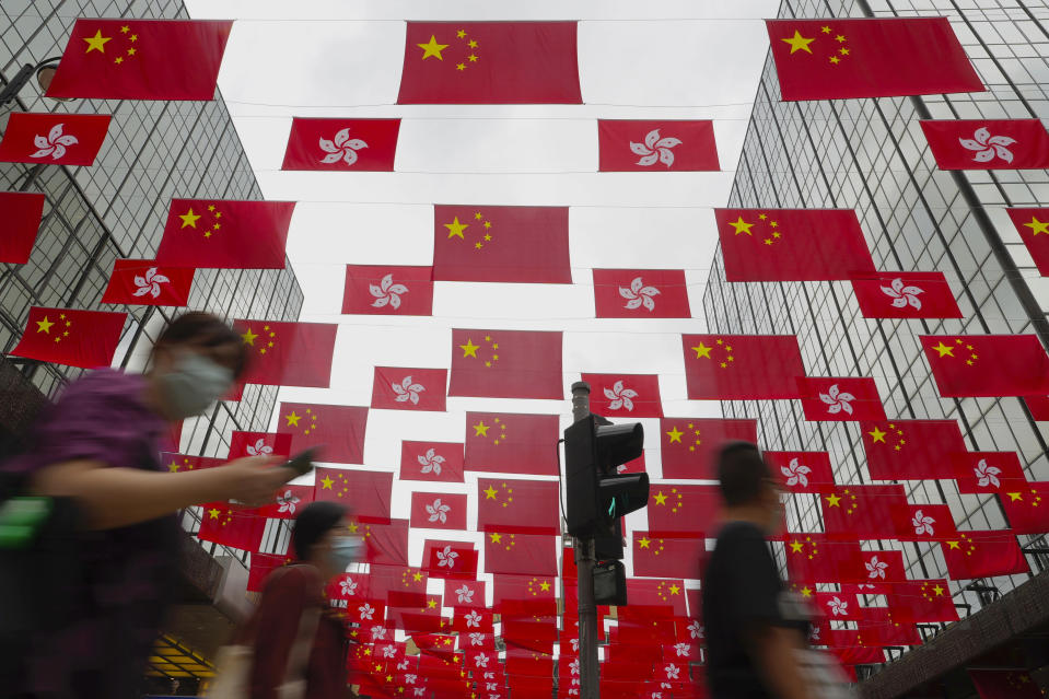 People walk past China national flags and Hong Kong flags for the celebration of 24th anniversary of Hong Kong handover to China at a shopping district in Hong Kong, Sunday, June 27, 2021. Fung Wai-kong, an editorial writer of the now-defunct Hong Kong pro-democracy newspaper Apple Daily was arrested at the airport on Sunday night while attempting to leave the city, local media reported Sunday. (AP Photo/Vincent Yu)