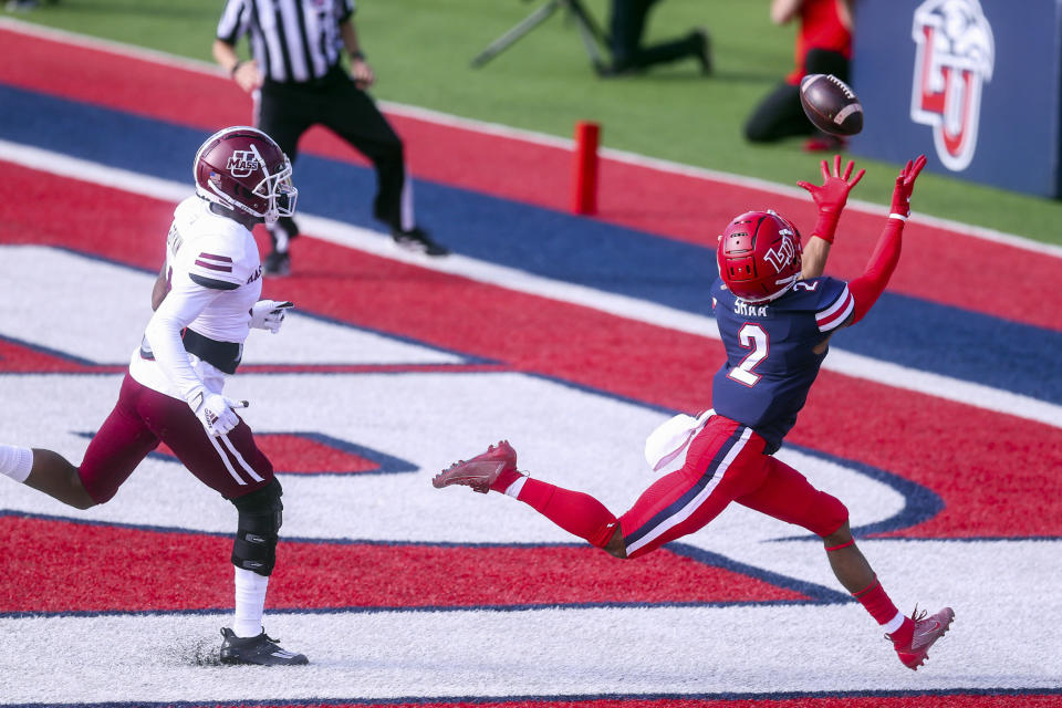 Liberty wide receiver Kevin Shaa (2) hauls in a touchdown pass in front of Massachusetts' Noah Boykin (4) during the first half of an NCAA college football game on Friday, Nov. 27, 2020, at Williams Stadium in Lynchburg, Va. (AP Photo/Shaban Athuman)