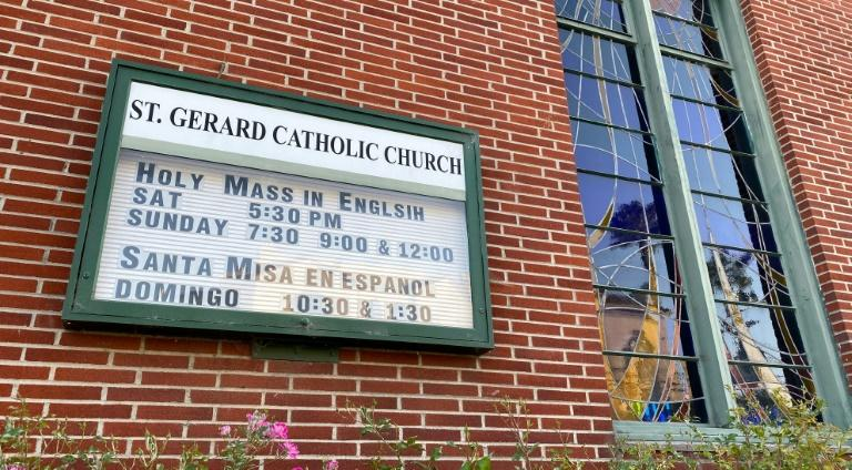 An old sign advertising the time for mass is seen on the facade of closed St. Gerard Majella Catholic church in Los Angeles on May 23, 2020 amid the coronavirus pandemic