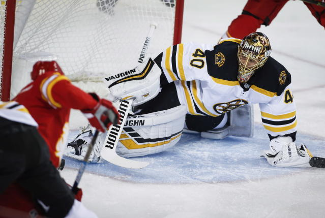 Boston Bruins goalie Tuukka Rask, right, of Finland, kicks the puck away on a shot from Calgary Flames' Mikael Backlund, of Sweden, during an NHL hockey game in Calgary, Alberta, Wednesday, Oct. 17, 2018. (Jeff McIntosh/The Canadian Press via AP)