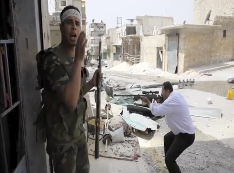 In this image made from video and accessed Saturday, Sept. 1, 2012, a Free Syrian Army fighter calls out to comrades as another fighter fires at Syrian Army positions in Aleppo, Syria. Syrian troops bombarded the northern city of Aleppo Saturday with warplanes and mortar shells as soldiers clashed with rebels in different parts of Syria's largest city, activists said. The Britain-based Syrian Observatory for Human Rights said the clashes were concentrated in several tense neighborhoods where some buildings were damaged and a number of people were wounded. (AP Photo via AP video)