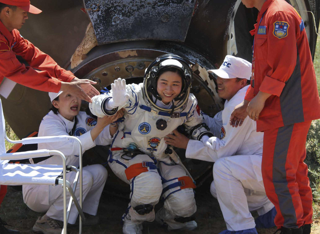 In this photo released by China's Xinhua news agency, China's first female astronaut Liu Yang waves as she comes out of the re-entry capsule of Shenzhou-9 spacecraft in Siziwang Banner of north China's Inner Mongolia Autonomous Region Friday, June 29, 2012. Liu and two other crew members emerged smiling from the capsule that returned safely to earth Friday from a 13-day mission to an orbiting module that is a prototype for a future space station. (AP Photo/Xinhua, Wang Jianmin) NO SALES