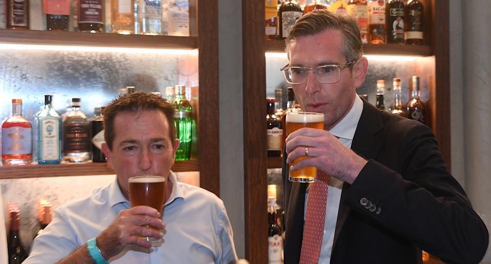 NSW Premier Dominic Perrottet and NSW Deputy Premier Paul Toole drinking a beer standing up, despite it being against public health orders. Source: AAP