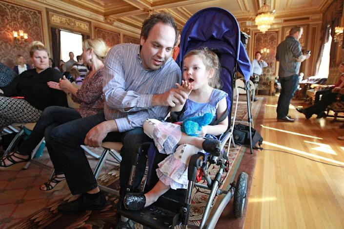 Clinton Atwater plays with his daughter Asia Skye Atwater, 7, before the H.B 105 bill signing ceremony at the Utah State Capitol Tuesday, March 25, 2014, in Salt Lake City. Parents of Utah children with severe epilepsy are cheering a new state law that allows them to obtain a marijuana extract they say helps with seizures, but procuring it involves navigating a thorny set of state and federal laws. Utah's Republican Gov. Gary Herbert has already approved the law and held the signing ceremony Tuesday afternoon. The new law doesn't allow medical marijuana production in Utah but allows families meeting certain restrictions to obtain the extract from other states. (AP Photo/Rick Bowmer)