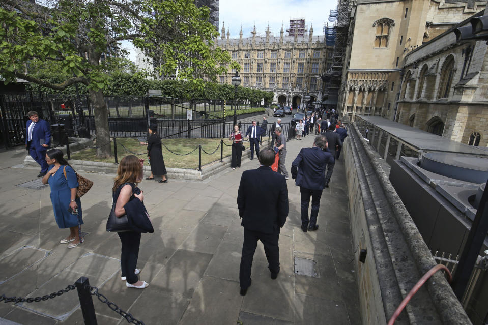 UK lawmakers queue outside the Houses of Commons in Westminster, London, Tuesday June 2, 2020. Prime Minister Boris Johnson's Conservative government faced a rebellion from some of its own legislators on Tuesday after it summoned Members of Parliament back to London and prepared to scrap a remote-voting system used during a nationwide coronavirus lockdown. (Jonathan Brady/PA via AP)