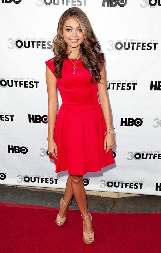 """""""Modern Family"""" co-star Sarah Hyland was red hot at Outfest's closing night gala in this sleeveless Ted Baker dress and nude Sam Edelman peep-toes. Freshly curled tresses and a smile completed her bright appearance. (7/22/2012)<br><br><a href=""""http://tv.yahoo.com/news/-modern-family--cast-sues-20th-tv-as-contract-renegotiation-turns-ugly--exclusive-.html"""">""""Modern Family"""" cast sues over salary dispute</a>"""