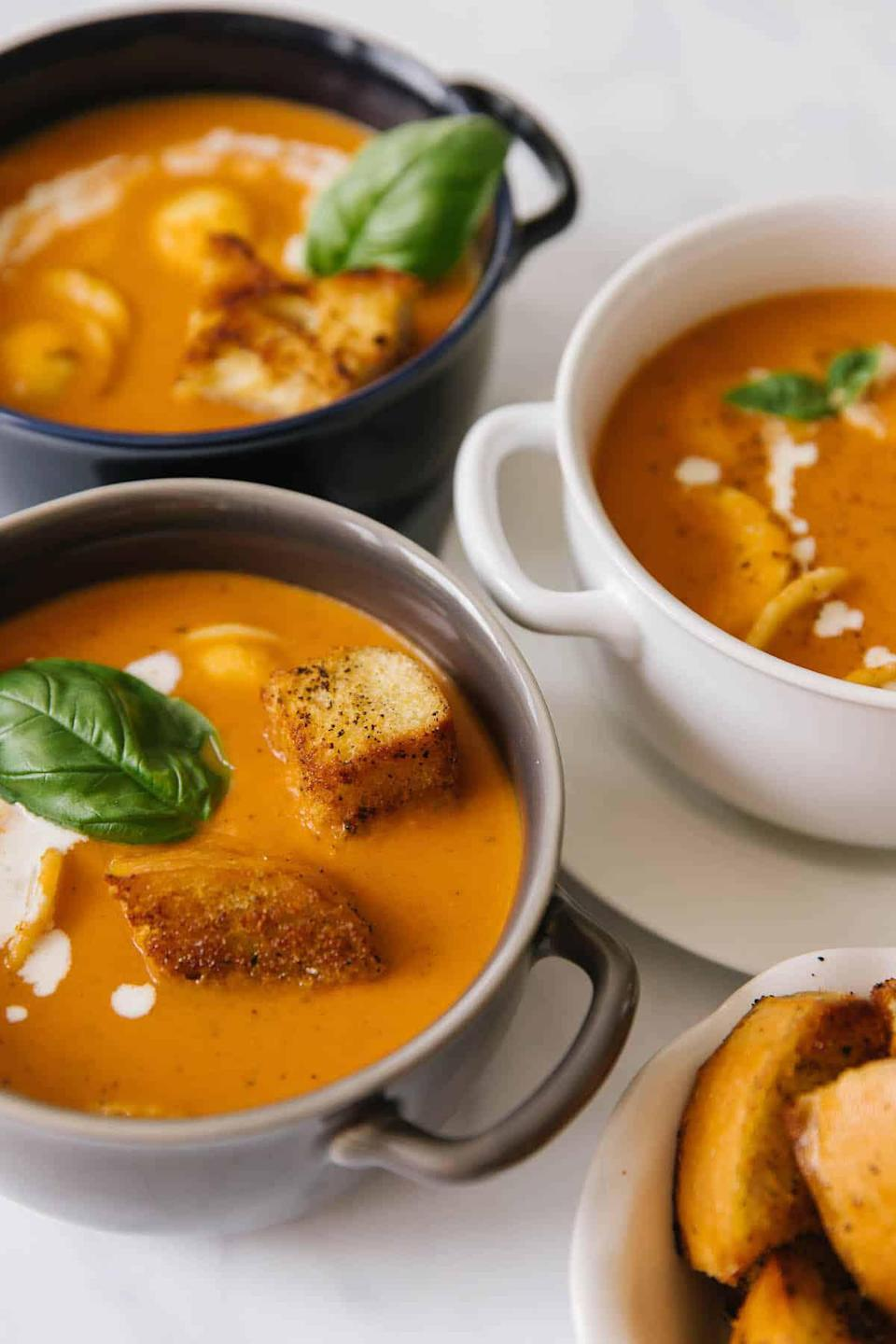 """<p>One of the best ways to combat cold weather is to eat a warm bowl of soup. This creamy tomato basil soup is the perfect comfort food you need to <a href=""""https://www.thedailymeal.com/best-recipes/15-soups-and-stews-will-keep-you-warm-winter-slideshow?referrer=yahoo&category=beauty_food&include_utm=1&utm_medium=referral&utm_source=yahoo&utm_campaign=feed"""" rel=""""nofollow noopener"""" target=""""_blank"""" data-ylk=""""slk:warm you up"""" class=""""link rapid-noclick-resp"""">warm you up</a>. Add the soup's ingredients to a slow cooker and let it do the cooking for you.</p> <p><a href=""""https://www.thedailymeal.com/best-recipes/tomato-basil-soup-freezer-homecooked-recipe?referrer=yahoo&category=beauty_food&include_utm=1&utm_medium=referral&utm_source=yahoo&utm_campaign=feed"""" rel=""""nofollow noopener"""" target=""""_blank"""" data-ylk=""""slk:For the Creamy Tomato Basil Soup recipe, click here."""" class=""""link rapid-noclick-resp"""">For the Creamy Tomato Basil Soup recipe, click here.</a></p>"""