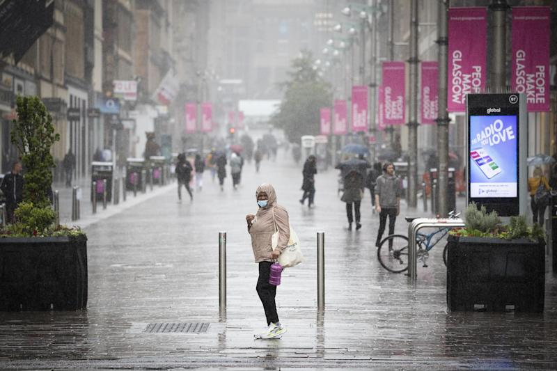 A file picture of a member of the public caught in heavy rain in Glasgow city centre: PA