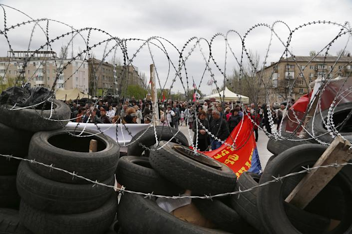 People stand at a barricade at the regional administration building that they had seized earlier in Donetsk, Ukraine, Sunday, April 20, 2014. The Ukrainian and Russian governments are reporting a shootout at a checkpoint set up by pro-Russian insurgents in eastern Ukraine that has left one person dead and others hospitalized with gunshot wounds. (AP Photo/Sergei Grits)