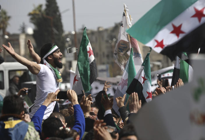 An anti-Syrian government protester shouts slogans as others wave revolutionary flags, to mark 10 years since the start of a popular uprising against President Bashar Assad's rule, that later turned into an insurgency and civil war, In Idlib, the last major opposition-held area of the country, in northwest Syria, Monday, March 15, 2021. (AP Photo/Ghaith Alsayed)