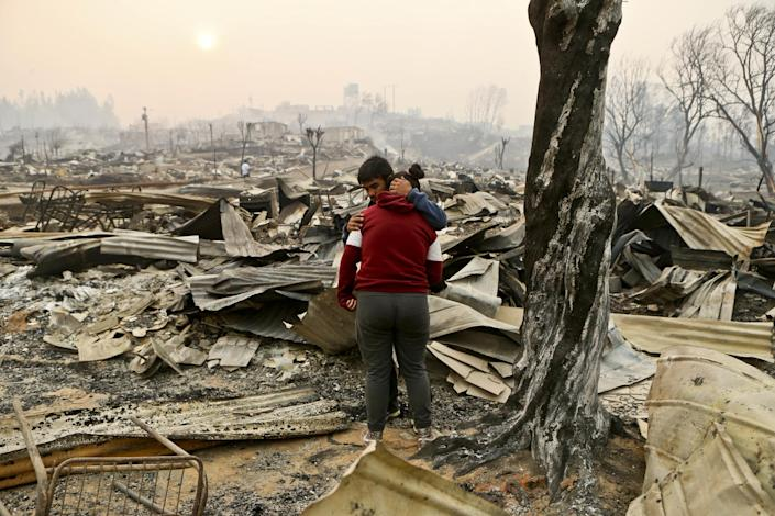 Juan Vega embraces his daughter where their home once stood after a wildfire in Santa Olga, Chile, Thursday, Jan. 26, 2017. Officials say the town was consumed by the country's worst wildfires, engulfing the post office, a kindergarten and hundreds of homes. (AP Photo/Esteban Felix)