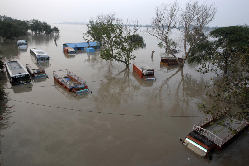 Buses and trucks are submerged in the rising waters of the Yamuna River in New Delhi, India, Wednesday, June 19, 2013. India's prime minister said Wednesday that the death toll from flooding this week in the northern state of Uttrakhand had surpassed 100 and could rise substantially. The flooding has affected several states and the capital New Delhi where nearly 2,000 people have been evacuated to government-run camps on higher ground. Authorities there said the situation would ease as the level of the Yamuna River was expected to start receding Thursday afternoon. (AP Photo/Tsering Topgyal)