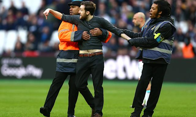 A pitch invader is escorted off the pitch during West Ham's game with Burnley.