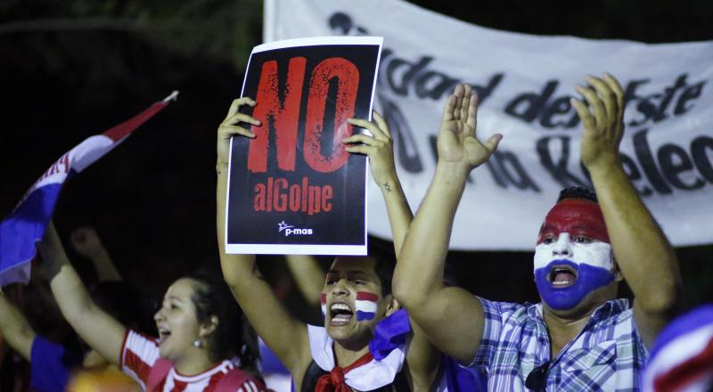 """A demonstrator holds a sign that reads in Spanish """" No to the coup"""" during a protest against the project to change the country's constitution, in Asuncion, Paraguay, Thursday, March 30, 2017. The country's upper house of Congress is split over a proposal to amend the constitution and allow for the re-election of former presidents. (AP Photo/Jorge Saenz)"""