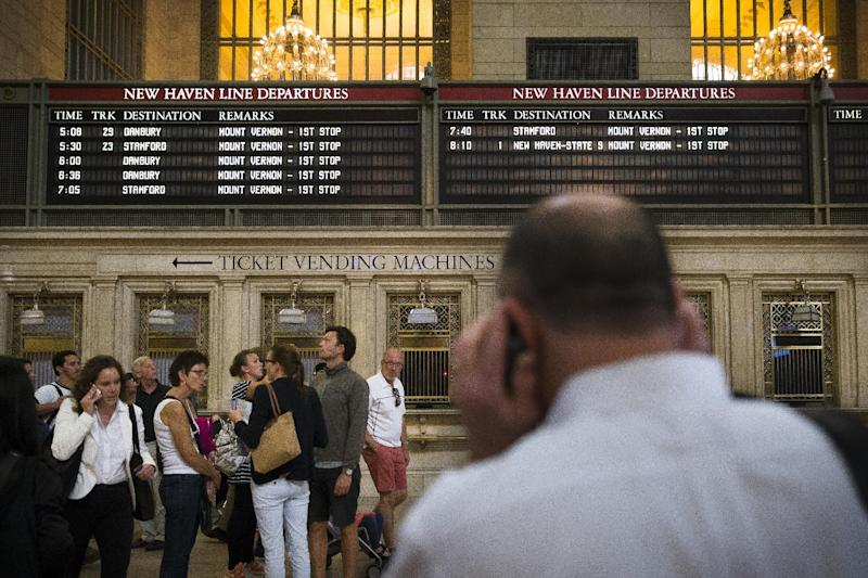 A depopulated New Haven transit line departures board looms over commuters as they use their cell phones at Grand Central Terminal, Wednesday, Sept. 25, 2013, in New York. Connecticut Gov. Dannel P. Malloy is warning commuters that it could take up to three weeks to fix broken equipment that has snarled service to and from New York City on the nation's second-largest commuter railroad. (AP Photo/John Minchillo)