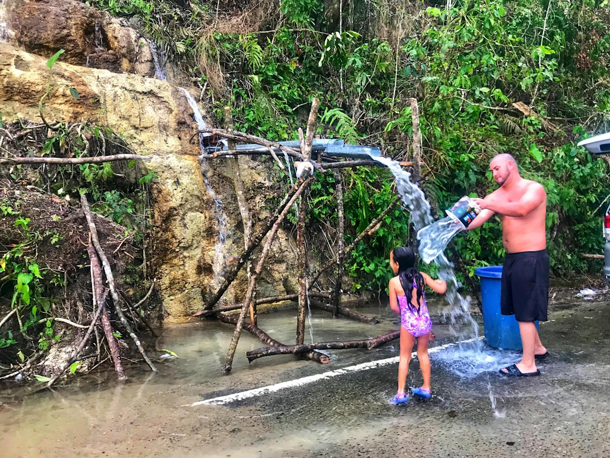 A young girl and her father rinse off in naturally flowing water from the side of a mountain in Ciales, Puerto Rico, on Oct. 11, 2017. (Photo: Caitlin Dickson/Yahoo News)