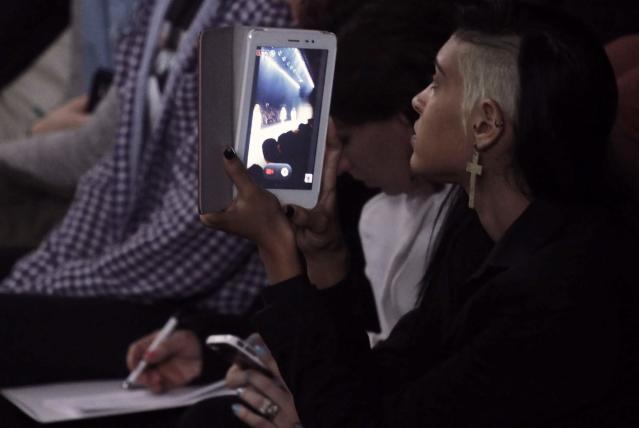 A spectator uses her tablet to record the Forum 2014 winter collection fashion show during Sao Paulo Fashion Week October 30, 2013. REUTERS/Nacho Doce (BRAZIL - Tags: FASHION SCIENCE TECHNOLOGY)
