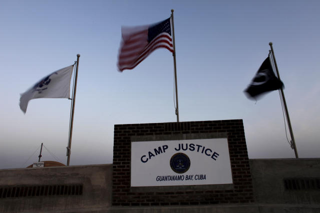 U.S. NAVAL BASE GUANTANAMO, CUBA - MAY 31: (EDITORS NOTE: IMAGE REVIEWED BY U.S. MILITARY PRIOR TO TRANSMISSION) Flags wave above the sign posted at the entrance to Camp Justice, the site of the U.S. war crimes tribunal compound on May 31, 2009 at U.S. Naval Base Guantanamo Bay, Cuba. Former child soldier Omar Khadr, the Canadian citizen captured on the battlefield in Afghanistan in 2002 is expected to appear in a military commission hearing tomorrow with the charge of providing support to terrorism after allegedly throwing a grenade that killed a US soldier. This trial marks the first hearing of the Bush-era war crimes tribunals to take place under U.S. President Barack Obama. (Photo by Brennan Linsley-Pool/Getty Images)