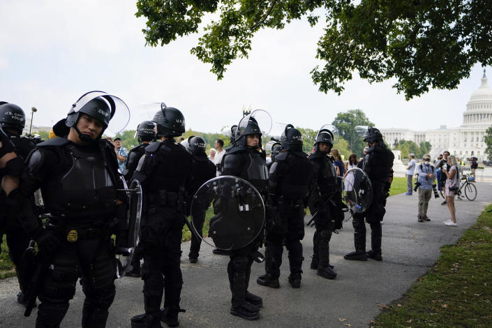 """Police in riot gear patrol during a rally near the U.S. Capitol in Washington, Saturday, Sept. 18, 2021. The rally was planned by allies of former President Donald Trump and aimed at supporting the so-called """"political prisoners"""" of the Jan. 6 insurrection at the U.S. Capitol. (AP Photo/Brynn Anderson)"""