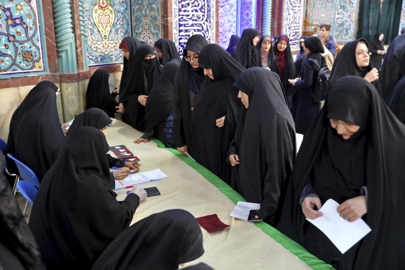 Voters register to cast their vote during the parliament elections at a polling station in Tehran, Iran, Friday, Feb. 21, 2020. Iranians began voting for a new parliament Friday, with turnout seen as a key measure of support for Iran's leadership as sanctions weigh on the economy and isolate the country diplomatically. (AP Photo/Ebrahim Noroozi)