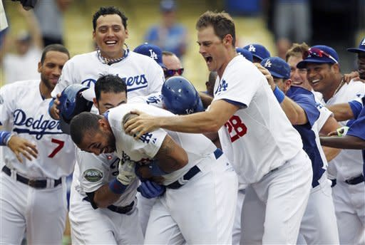 Los Angeles Dodgers' Matt Kemp, center, is swarmed by teammates, including Jamey Wright (28), after hitting a walkoff home run to give the Dodgers a 5-3 win over the Philadelphia Phillies in the 12th inning of a baseball game in Los Angeles, Wednesday, July 18, 2012. (AP Photo/Reed Saxon)