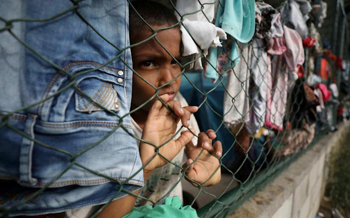 A child looks through a fence at a community center in Arauquita, Colombia, where thousands of Venezuelans are seeking shelter - AP Photo/Fernando Vergara
