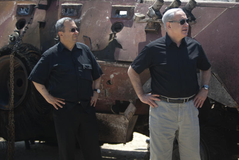 Israeli Prime Minister Benjamin Netanyahu, right, and Israel's Defense Minister Ehud Barak stand next to the wreckage of an Egyptian military vehicle after militants burst it through a security fence into Israel from Egypt, at an Israeli military base along the border with Egypt, southern Israel, Monday, Aug. 6, 2012. Officials say Egypt has deployed at least two helicopter gunships to the Sinai Peninsula in the hunt for militants behind the killing of 16 Egyptian soldiers at a checkpoint along the border with Israel. Suspected Islamists on Sunday evening attacked the Egyptian checkpoint, killed the troops, then stole two of their vehicles and burst through a security fence into Israel. Israeli aircraft then halted their assault. (AP Photo/Ariel Schalit)