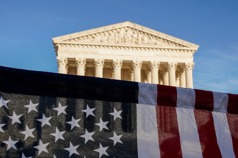 FILE PHOTO: A U.S. flag is seen during a demonstration before a vote on the nomination of Amy Coney Barrett to the Supreme Court in Washington