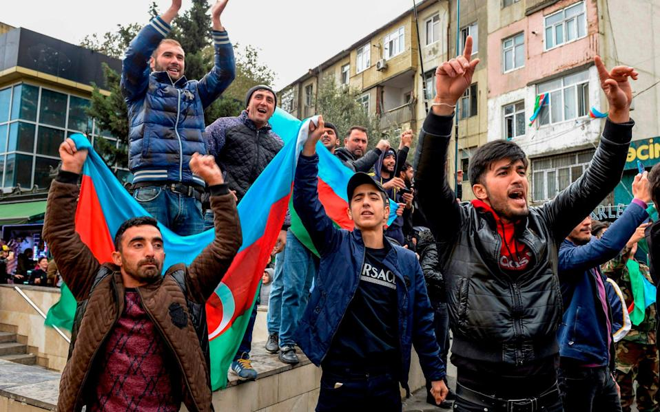 People hold Azeri flag as they celebrate the capture the town of Shusha in Baku - TOFIK BABAYEV/AFP