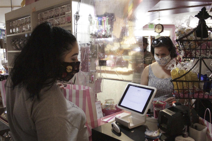 In this Thursday, May 28, 2020, photo, an employee at Bruce's Candy Kitchen ring up a customer's purchases from behind a protective plastic shield as both wear face masks due to the coronavirus in Cannon Beach, Ore. With summer looming, Cannon Beach and thousands of other small, tourist-dependent towns nationwide are struggling to balance fears of contagion with their economic survival in what could be a make-or-break summer. (AP Photo/Gillian Flaccus)