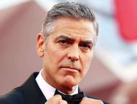 """U.S. actor Clooney adjusts his bowtie as he arrives for the premiere of """"Gravity"""" at the 70th Venice Film Festival"""
