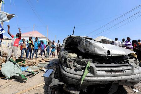 Civilians stand near a car destroyed in a suicide bomb explosion at the Wadajir market in Madina district of Somalia's capital Mogadishu, February 19, 2017. REUTERS/Feisal Omar