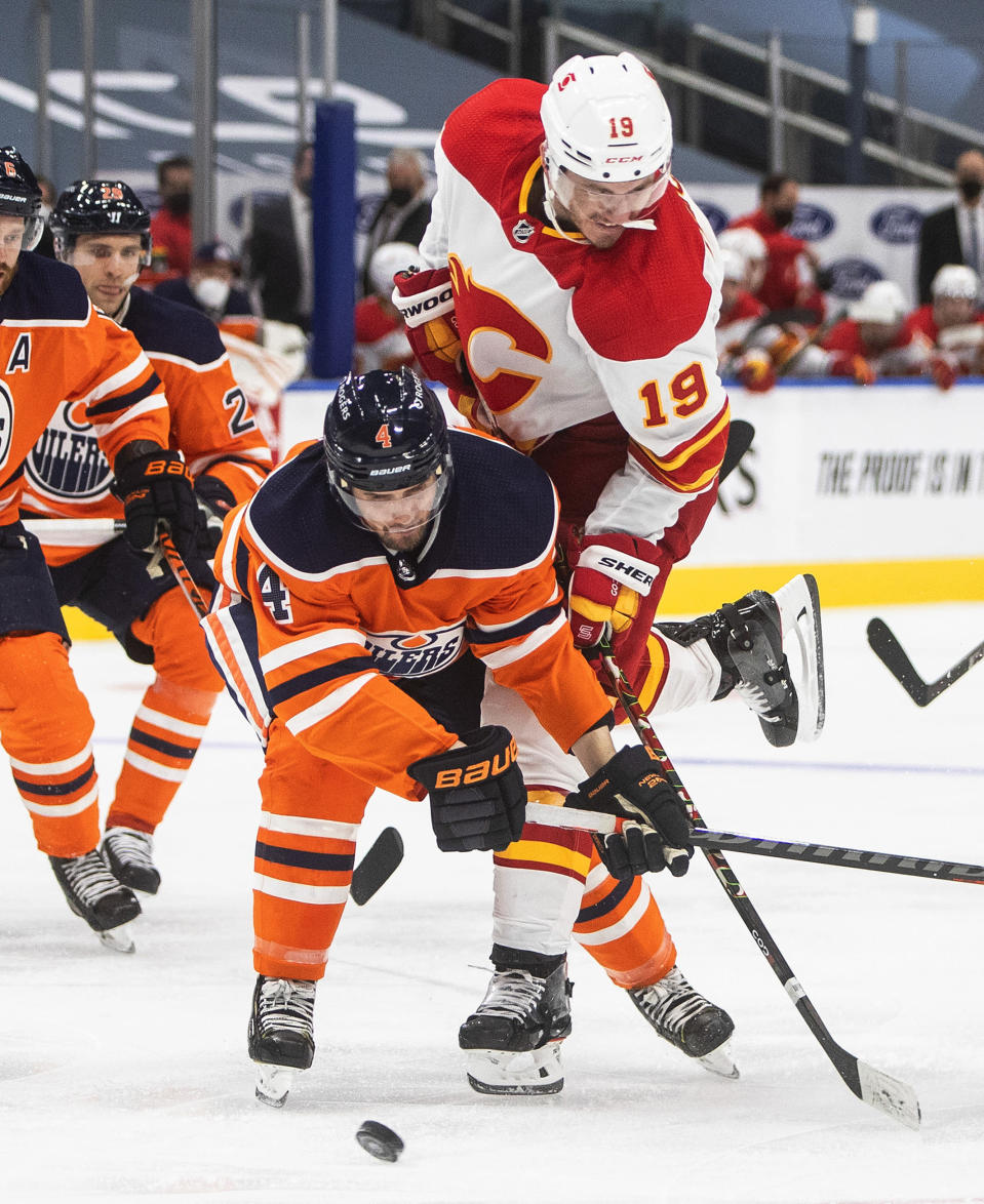 Edmonton Oilers' Kris Russell (4) and Calgary Flames' Matthew Tkachuk (19) vie for the puck during the third period of an NHL hockey game Friday, April 2, 2021, in Edmonton, Alberta. (Jason Franson/The Canadian Press via AP)