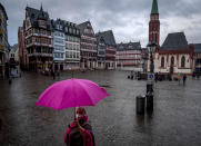 A woman wears a face mask and carries a pink umbrella as he walks over the Roemerberg square in Frankfurt, Germany, Thursday, Jan. 28, 2021. Further restrictions to avoid the outspread of the coronavirus are discussed Thursday by the German government. (AP Photo/Michael Probst)