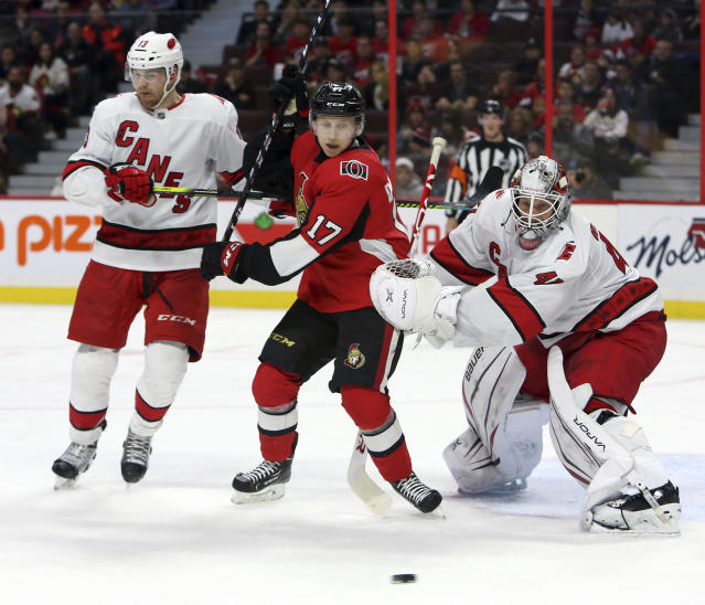 Ottawa Senators Jonathan Davidsson(17) and Carolina Hurricanes goaltender James Reimer(47) and forward Warren Foegele(13) keep their eyes on a loose puck during second period NHL hockey action in Ottawa, Saturday Nov. 9, 2019. (Fred Chartrand/The Canadian Press via AP)