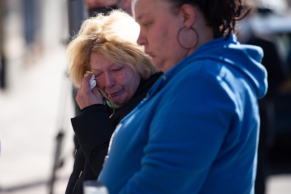 People are seen visibly upset at the scene on High Street, Brownhills, near Walsall in the West Midlands, where a two-week-old baby boy in a pram was hit by a BMW.