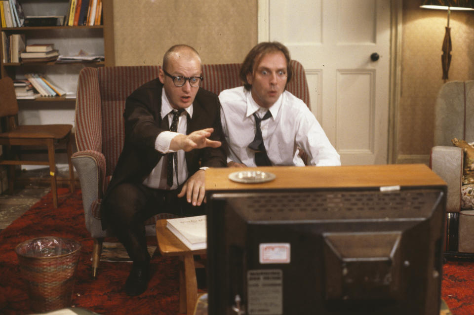 Comic actors Adrian Edmondson (left) and Rik Mayall watching television in scene from episode 'Contest' of the BBC television sitcom 'Bottom', June 24th 1990. (Photo by Don Smith/Radio Times/Getty Images)