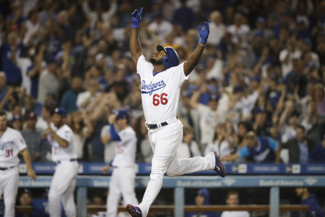 Yasiel Puig celebrates his three-run home run during the seventh inning against the Rockies. (AP)