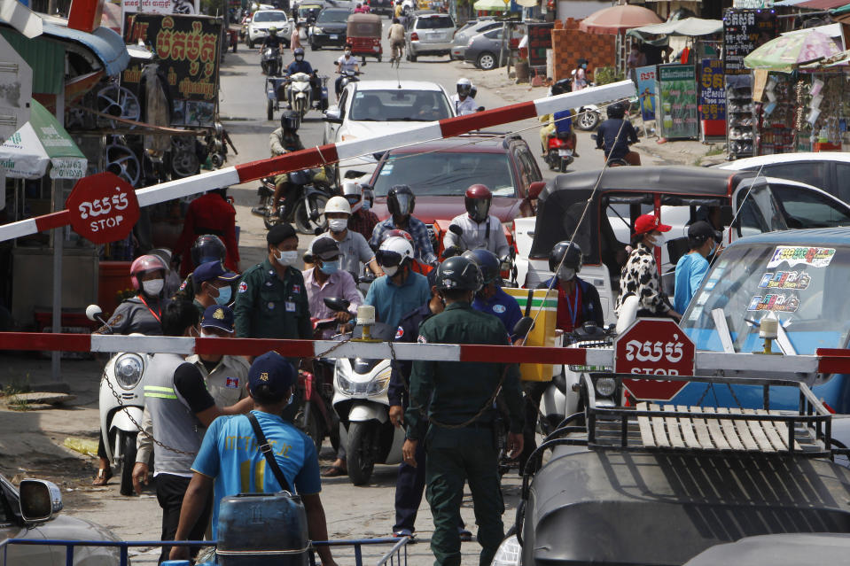 People are blocked by local police officers to get into the main city street near Phnom Penh International airport in Phnom Penh, Cambodia, Thursday, April 15, 2021. Cambodia's leader said that the country's capital Phnom Penh will be locked down for two weeks from Thursday following a sharp rise in COVID-19 cases. (AP Photo/Heng Sinith)