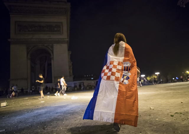 BOR115. Paris (France), 15/07/2018.- A woman wearing a Croatian flag walks alone near the Champs-Elysees avenue after the victory of France at the FIFA World Cup 2018 final match against Croatia in Paris, France, 15 July 2018. (Croacia, Mundial de Fútbol, Francia) EFE/EPA/IAN LANGSDON
