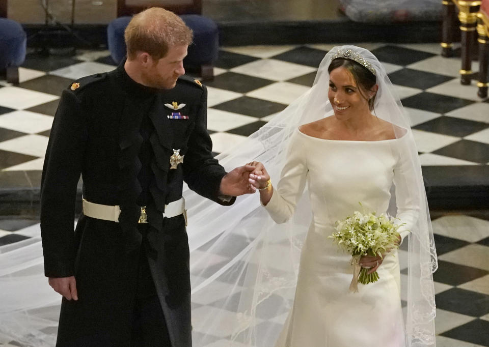 Britain's Prince Harry, Duke of Sussex (L) and Britain's Meghan Markle, Duchess of Sussex, (R) walk away from the High Altar toward the West Door to exit at the end of their wedding ceremony in St George's Chapel, Windsor Castle, in Windsor, on May 19, 2018. (Photo by Owen Humphreys / POOL / AFP)        (Photo credit should read OWEN HUMPHREYS/AFP via Getty Images)